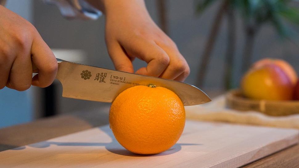 オレンジを包丁で切る