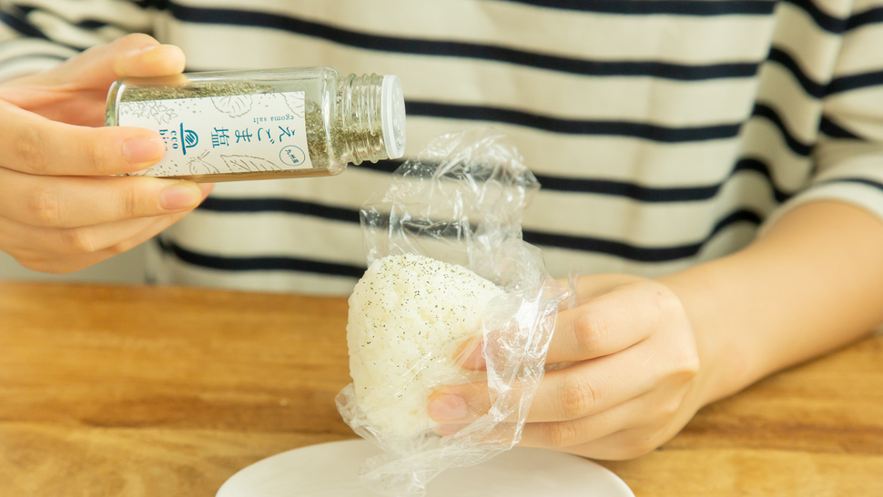 woman-put-salt-on-riceball
