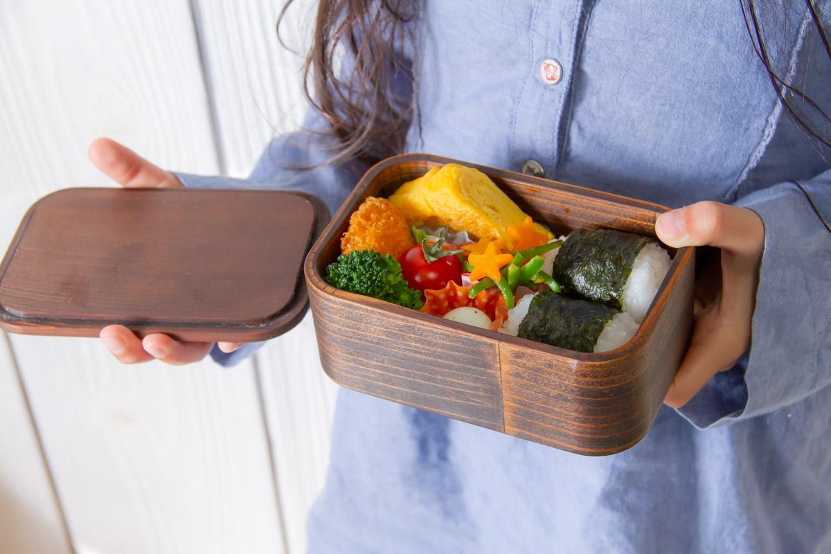 お弁当箱を持つ小学生の女の子