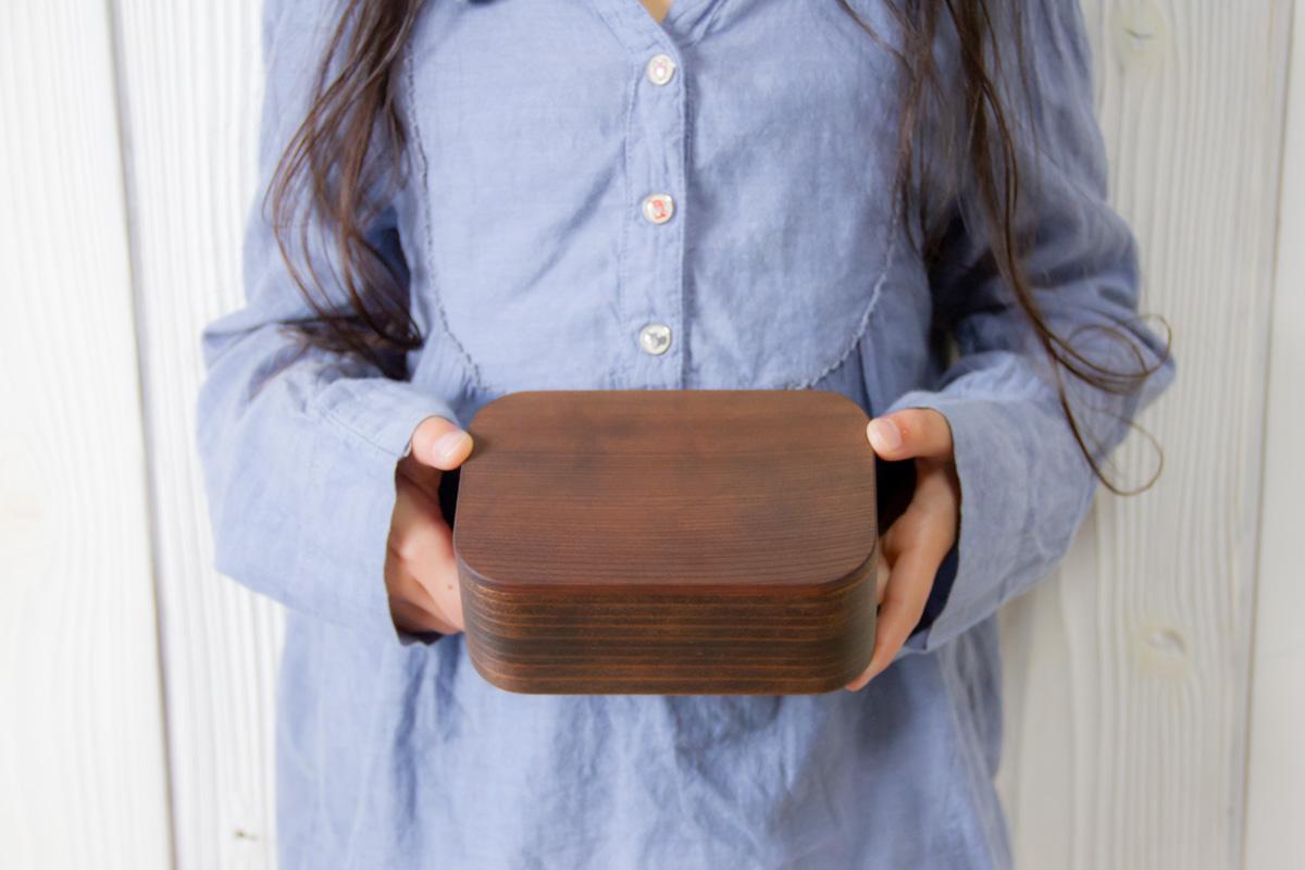 両手でお弁当箱を持つ女の子